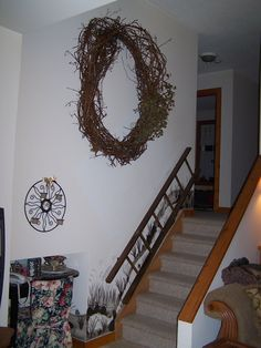 Make an enormous grapevine wreath for that very large bare wall... Decorate to suit.. Remember less is more... SuZDo