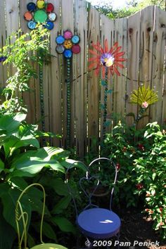 fence flowers made from paint can lids, bottle caps and mirrors.