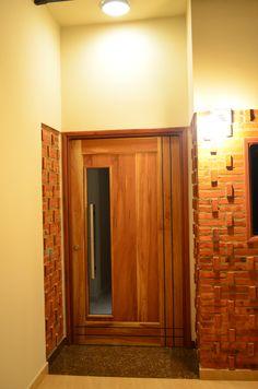 Diseño de ladrillo visto en acceso principal, puerta principal pivotante de madera maciza y vidrio templado de 10mm, iluminación