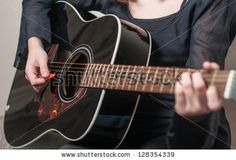 Female hand playing acoustic guitar.guitar play.Close up of guitarist hand playing acoustic guitar by Iancu Cristian, via ShutterStock