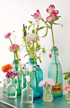 Flowers in blue glass bottles.