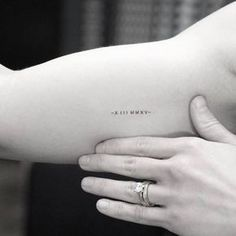 Minimalist date tattoo in roman numerals on the right inner arm.