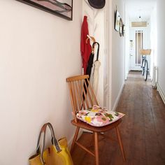 Slim hallway with wooden floor, chair and hooks