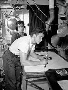 Strapping young Canadian Able Seaman plotting radar coordinates while on the water during the summer of 1941.