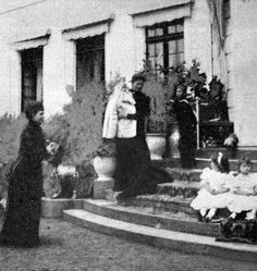 Empress Alexandra holding baby Maria with Olga and Tatiana posing on the steps and the Dowager Empress looking on
