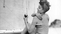 A 1950s woman on a sailboat applies sunscreen.
