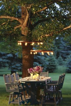 LOVE this outdoor dining space! Fun ideas to use the bar height outdoor table and chairs under the tree (and those lights!)...