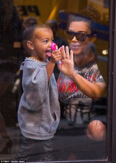 Helping hand: Kim smiled and reached out as North stuck out her tongue
