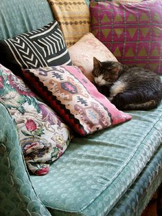"Colorful mix of patterned pillows - Vintage / old teal green ""granny"" sofa - Sleeping cat"