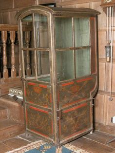 "1711 ""This is probably to second oldest surviving sedan chair in the United Kingdom. It is a standard Louis XIV Parisian public hire chair which has been specifically painted for use around the royal residence of Chateau Marly (demolished early 19th century), five miles north of Versailles. The majority of these sedan chairs have not survived as they were broken down, burnt or given for use in hospitals during the French Revolution."""