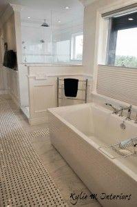 Beautiful ensuite bathroom with marble basketweave floor, walk in shower, wainscoting and freestanding tub