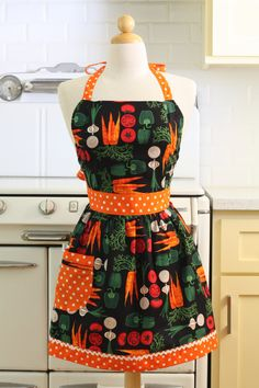 This is a very cute vintage inspired full apron! This apron is in a black veggie print. The pocket and straps are in an orange and white dot with white
