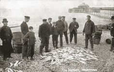 Fishermen with their catch on the beach, Worthing. A group of fishermen wearing working clothes and caps stand around their catch of fish displayed on the pebbles. One man smokes a pipe. Two young boys stand in the group. Baskets on beach. Worthing pier with south pavilion in background. Terry Child Collection. Young Ones Project. ImageDate 	c1900 Man Smoking, Young Ones, Old Photos, Past, England, Worthing, Beach, Pictures, Pavilion