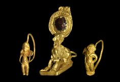 Hellenistic Period, 323-146 BC. A mixed group of gold earrings comprising: a garnet set en cabochon on a discoid plate with filigree surround attached to a gold model sphinx, crouching on a tongue-shaped base with loop to rear; a wire with cast model cherub with hands on hips and splayed wings; a wire with cast model figure with hands on hips. Gold and garnet.