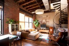 Loft living room with floor cloth, neutral palette, spiral staircase, sectional, exposed brick walls - By Chris A. Dorsey in Brooklyn, NY