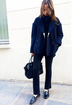Columbine Smille wears a blue coat, black sweater, flared pants, a tote bag, and loafers