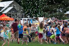 World photo/Don Seabrook:   A garbage sack full of ping pong balls falls on heads and in sacks of children grouped below the helicopter from where they came at Saturday's Celebrate Cashmere festival. The kids turned in the balls they gathered for prizes