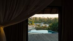 Stock Footage of A slow linear dolly shot from the inside of a luxurious private African lodge with a view onto the patio deck with swimming pool and river in the distance just after dawn, at sunrise. Explore similar videos at Adobe Stock Stock Video, Stock Footage, Valance Curtains, Distance, Dawn, Swimming Pools, Sunrise, Shots, African