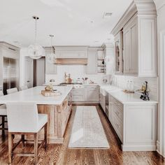 Love the addition of the wood to island and how it matches with stove floor and chairs and accents in cabinets I want something similar with darker brown and maybe less white backsplash