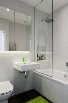 In the bathroom of this flat, the architects replaced all of the old fittings and added white square tiles to the walls.