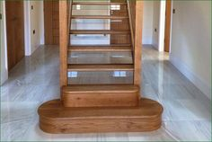 Roger Hill Staircase - American white oak staircase with a bullnose on a large D-end step, with glass balustrading throughout.