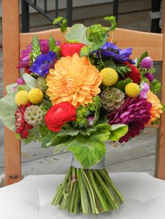 Bright and colorful autumn wedding bouquet of orange and purple dahlias, yellow craspedia, red ranunculus and zinnias, scabiosa pods, blue anemone.