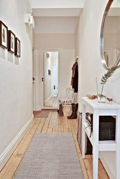 Luminoso y moderno #pasillo decorado con paredes blancas y #suelo de #madera