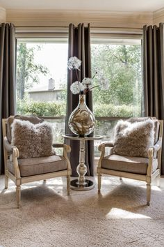 Two French country-style armchairs are adorned with furry pillows and situated in front of large windows, creating an ideal spot for intimate conversation. In between the chairs, a metallic table boasts a metallic vase, adding an eye-catching splash of glamor to the space.