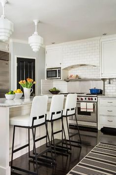 Stunning white kitchen features an ebony wood floor covered with a black and white striped rug placed behind three Lawson Fenning Elysian Barstools positioned in front of an ivory island complemented with a gray and white marble countertop illuminated by two vintage white glass pendants.
