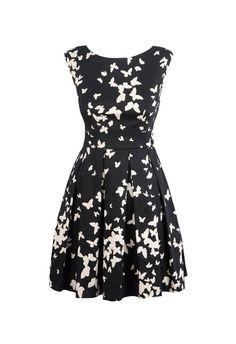 Zwarte jurk met witte vlinderprint. Mooie V-uitsnijding op de rug.De rok staat iets wijder open door de platte plooien onder de taille.
