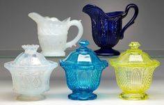 Numerous colored lacy-period creamers and covered sugar bowls several ex-Elsholz collection.