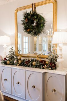 Christmas dining decor ideas. Gold ornate mirror with wreath hanging with Frontgate ribbon and white marble lamps. Flocked Christmas Trees, Christmas Decorations, Holiday Decor, Blue Christmas, Christmas Stuff, Seasonal Decor, Christmas Wreaths, Christmas Gifts, Home Decor Inspiration