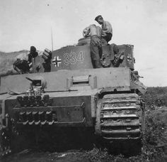 The crew of Tiger 1 nr.334 making an inspection of their vehicle in a rear area.