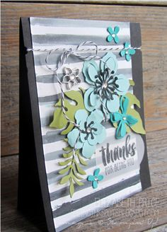 Black water colored stripes on Shimmer White Paper using Aqua Painter, Momento Ink Refill, and Stripes Stencil. Teal and aqua Botanical Builder Framelit flowers along with Botanical Jewel and Basic Rhinestones. Suite Sayings stamp set on Vellum Card Stock and a Basic Black Bakers Twine