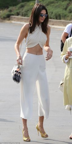 Kendall Jenner was certain to raise eyebrows with her cream white halter top and cropped white trousers (by O'2nd wrap cropped pants £205.61) as she arrived to church in West Hills