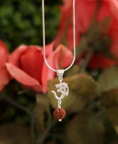 Sterling silver necklace depicts the Om symbol. Embellished with the Rudraksha bead, the necklace measures 18 inches in length.