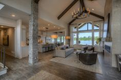 Large great room with stone pillar, ceiling beam detail. Lake feel.