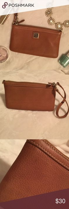 """Dooney & Bourke Brown Leather Wristlet Authentic Dooney & Bourke pebbled leather wristlet in good condition. Approximately 7.5""""x4.5"""". Used only a few times! Has a small pen mark on back (shown in photo- hard to see!) Dooney & Bourke Bags Clutches & Wristlets"""
