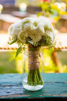 Ivory ranunculus and seeded eucalyptus were wrapped with a natural, raffia ribbon.