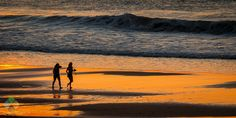 Walking on the beach - Two girls walking on the beach at sunset, while the last rays of the sun fade over the horizon.