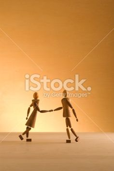Two wooden figures shake hands. These are unique and original wooden.