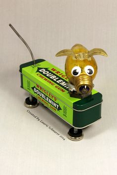 """""""Wrigley"""" ~ Original junk art created by Laurie Schnurer in 2014. Tin opens to store things inside. The best part is the tail, being a spring, once you touch it it just wags and wags. :)"""
