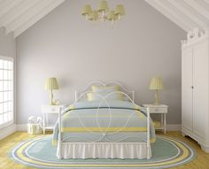 An elegant bedroom in blue and yellow with gray walls. A large window on the left wall