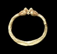 A gold Bracelet with bird-shaped terminals   Persia, 11th-12th Century  of circular form, with central pin fastening, hinge to one side of band, each bird with delineated wing and eye and granulated decoration   8.2cm diam.; 15g.