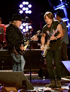 Musicians John Anderson (L) and Keith Urban perform onstage during ACM Presents: Superstar Duets at Globe Life Park on April 18, 2015 in Arlington, Texas.