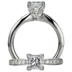 Ritani Setting diamond engagement ring featuring a prong set princess cut centerstone that is surrounded by microset diamonds set within the mini heart prongs and micropavé diamonds on the prongs.  Finishing this ring is the single row graduated pavé diamond shank.