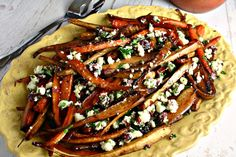 """Roasted parsnips and carrots topped with a little feta cheese """"salad"""" of lemon, parsley, and dried cherries, make for a very refreshing side dish."""