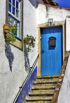 Blue door in Obidos, Portugal http://www.nomad-chic.com/runaway-blues-comme-des-garcons.html