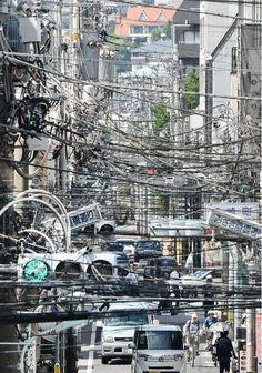 Cables Over Japanese Streets. Look to the sky and you'll surely notice the many electrical wires, transmission lines, TV cables, fiber optic lines and every other carrier of modern-day technology.There's a certain shopping street (known as shotengai in Japanese) where cables are so dense they almost obstruct the entire overhead. City Landscape, Urban Landscape, Bg Design, Japanese Streets, Shopping Street, Cyberpunk, Science Fiction, Cities, City Photo