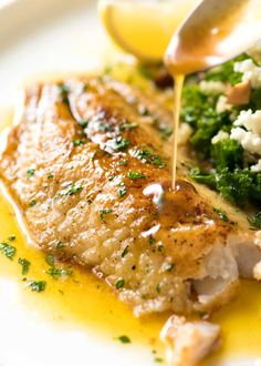 Lemon Butter Sauce being poured over crispy pan fried fish on a white plate.